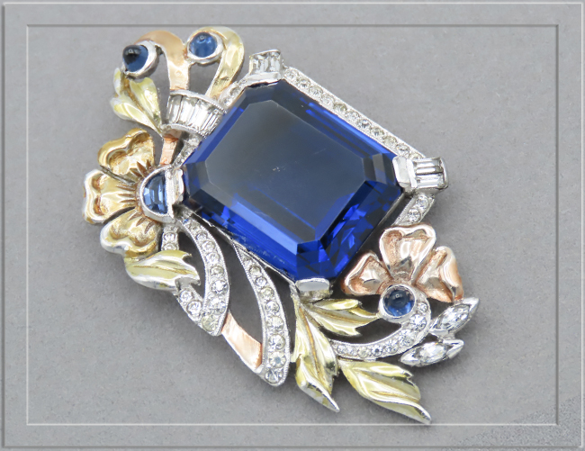 Glass sapphire set in tri-gold tone setting with sapphire bullet cabochons