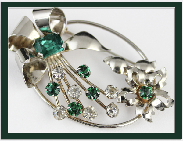 A LOVELY STERLING BROOCH in a floral design with emerald green and clear rhinestones